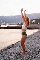 Young woman standing on stony beach with outstretched arms dancing photo