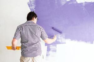 Hombre colorear pared con rodillo con pintura violeta foto