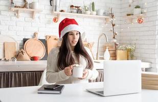 Mujer con gorro de Papá Noel charlando con amigos usando su computadora portátil foto