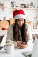 Mujer con gorro de Papá Noel charlando con amigos usando su teléfono móvil foto