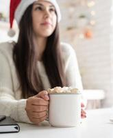 Brunette woman in santa hat holding a cup of marshmallow cocoa photo