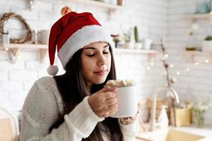 Woman in santa hat holding a cup of marshmallow cocoa in the kitchen photo
