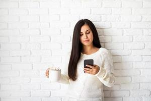 Woman holding a cup of marshmallow cocoa and her phone photo