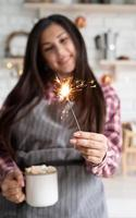 Woman with a cup of marshmallow cocoa and a sparkler photo