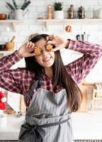woman in apron holding star shaped cookies in front of her eyes photo