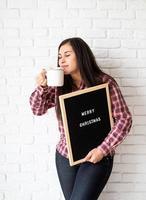 Mujer con gorro de Papá Noel con tablero de letras negro foto
