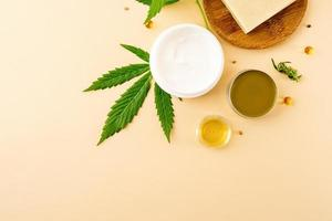 El aceite de cbd y el cannabis deja la vista superior de los cosméticos sobre fondo naranja foto