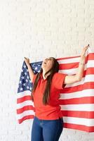 Beautiful young laughing woman with American flag, arms outstretched photo