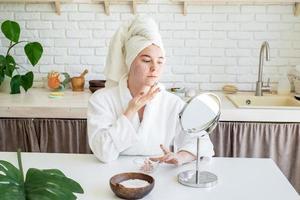 mujer aplicando crema facial en casa foto