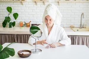 mujer aplicando exfoliante facial en la cara foto