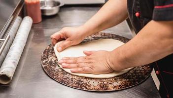 Baker hands making dough for pizza photo