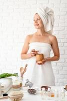 Woman in white bath towel using marble mortar and pestle photo