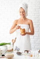 Woman in white bath towel doing spa procedures photo