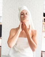 Mujer haciendo maquillaje matutino aplicando crema facial mirando al espejo foto