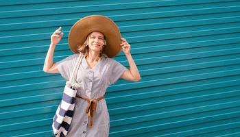 mujer de pie en la calle junto a la pared azul en un día ventoso foto
