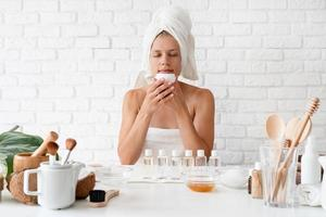 Woman in white bath towel smelling the creme doing spa procedures photo