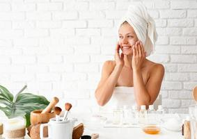 Woman in white bath towel applying face cream doing spa procedures photo