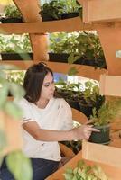 mujer sentada en el sofá en el centro comercial, mirando las plantas foto