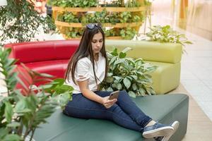 mujer sentada en el sofá en el centro comercial, mirando el teléfono foto
