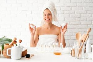 Woman in white bath towels smelling the cream doing spa procedures photo