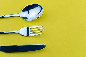 Set of fork, knife and spoon isolated on yellow paper background. photo