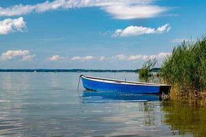 Bote de remos se encuentra a orillas del chiemsee en Baviera con juncos foto
