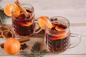 Hot mulled wine with spices in glass cup on wooden background. photo