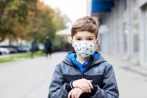 Child wears face mask in the city during coronavirus pandemic. photo