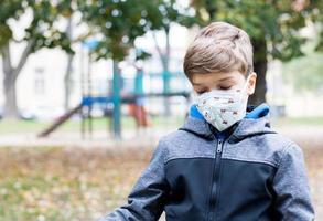 niño pequeño se siente solo en el patio de recreo durante la pandemia de coronavirus. foto