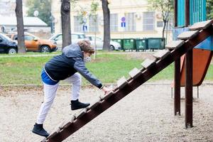 Kid playing o playground and wears face mask due to COVID-19 pandemic. photo