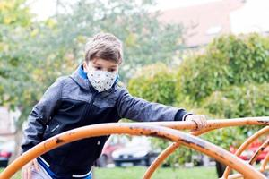 Boy with  face mask while playing on the playground. photo