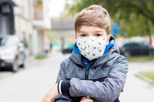 Child with protective face mask due to coronavirus pandemic. photo