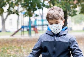 Lonely boy with face mask feels sad at playground due to coronavirus photo