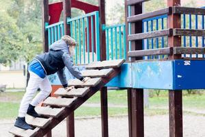 Small boy playing alone on the playground due to coronavirus pandemic. photo