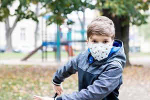Small boy wearing protective face mask in the park. photo