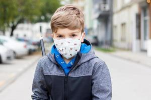 Portrait of a boy with protective face mask on city street. photo