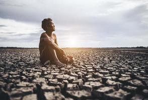 An elderly man sat hugging his knees bent on dry soil photo