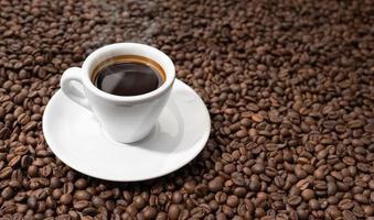 Taza de café expreso sobre fondo de granos tostados. copia espacio foto