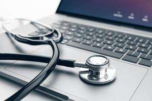 Stethoscope on modern laptop computer. Online health care concept photo