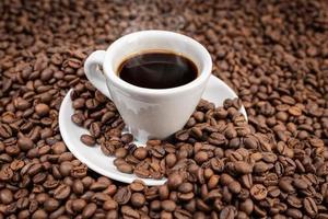Taza de café expreso sobre fondo de granos tostados foto