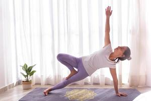 A young woman performs a yoga asana one legged side plank photo