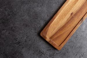 Wooden cutting board on black table background photo
