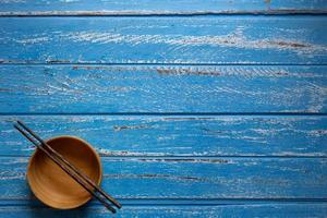 Chopsticks and empty wooden bowls on blue table background photo