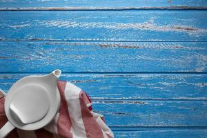 Tetera de cerámica blanca sobre fondo azul de la tabla foto