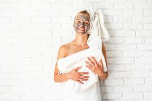 Woman wearing and holding bath towels with a clay facial mask on her face photo