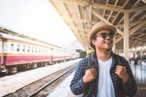 Young Asian Traveler backpack in train station photo