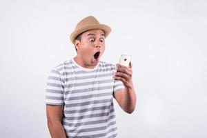 Shocked and surprised asian man looking smartphone photo