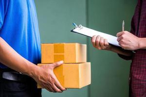 cerrar las manos masculinas que firman para recibir su paquete del repartidor. foto