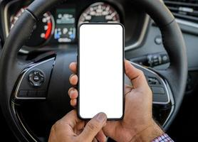 Hand holding blank screen of smartphone while driving car. photo