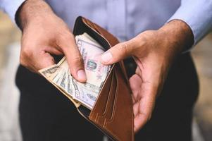 Business man holding the money in wallet photo
